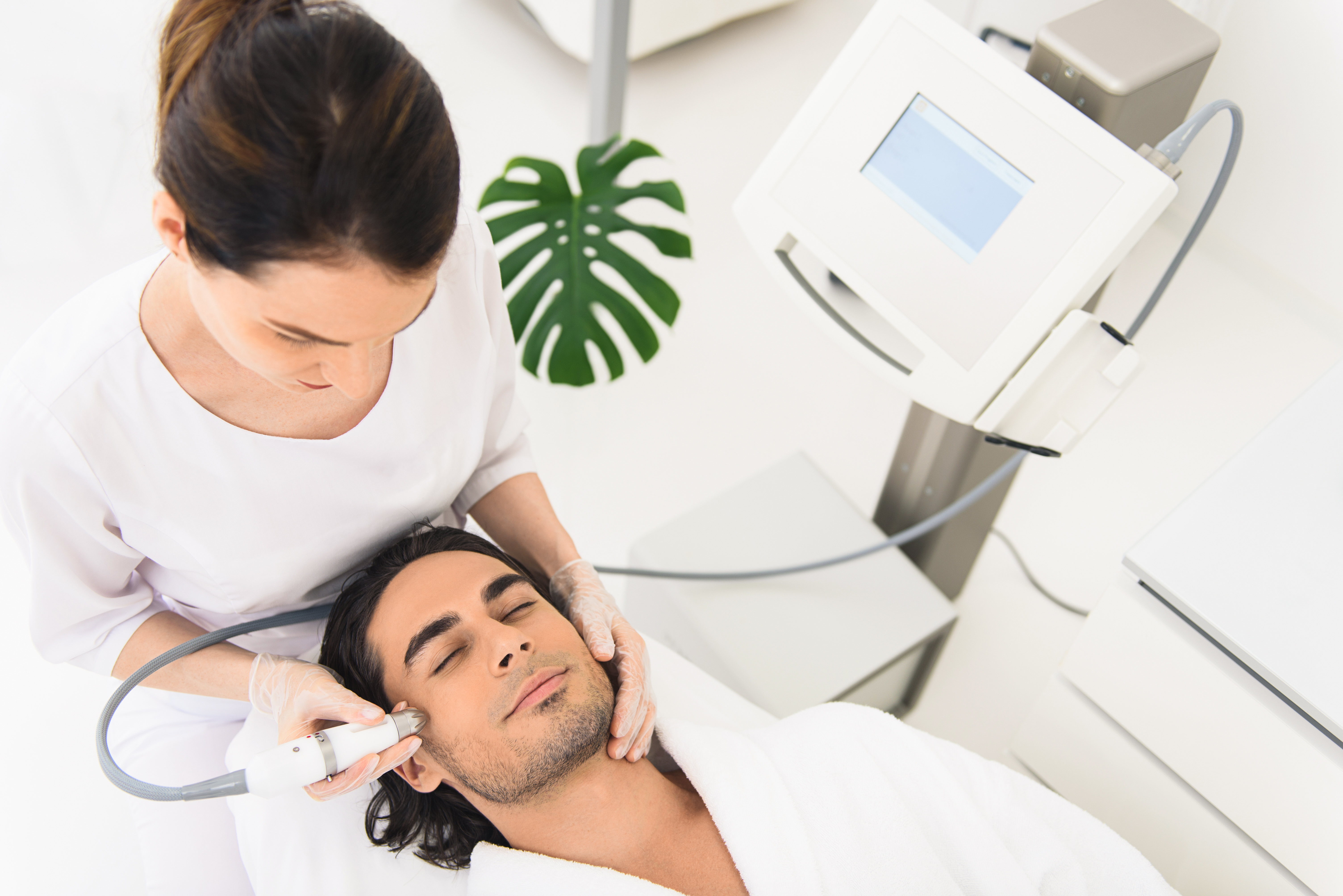 male client having laser facial treatment in beauty salon